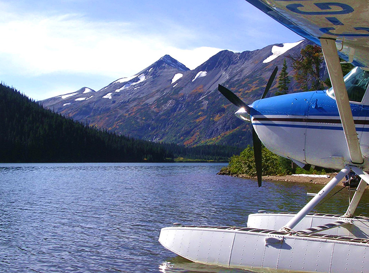 Front of a floatplane on a lake in the mountains